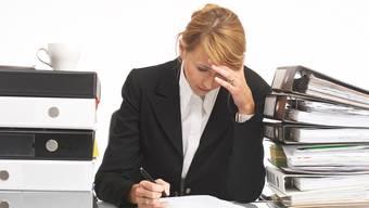 erschöpfte Geschäftsfrau sitzt an einem Tisch voller Büroarbeiten