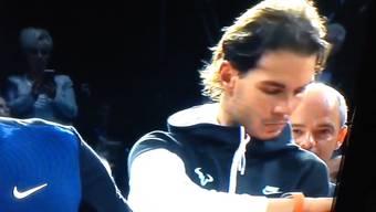 Roger Federer sonnt sich im Ruhm – derweil schaut Nadal im Hintergrund genervt auf die Uhr.