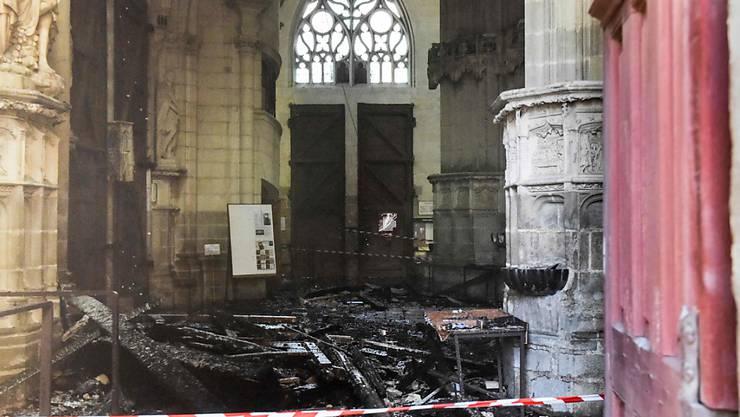 Verkohlte Trümmer liegen in der Kathedrale von Nantes. Foto: Sebastien Salom-Gomis/AFP/dpa