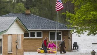 Einwohner in Beaverton im US-Staat Michigan bewegen sich nach Überschwemmungen auf Gummibooten vorwärts.