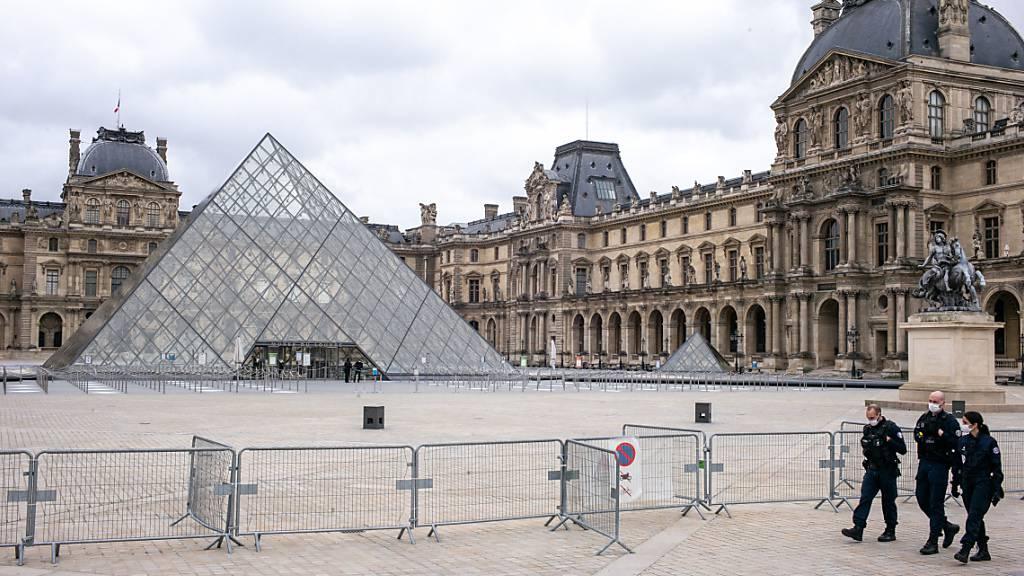 ARCHIV - Der Louvre ist geschlossen, der Platz davor ist leer. Nur drei Polizisten gehen an einer Absperrung entlang. Foto: Elko Hirsch/dpa