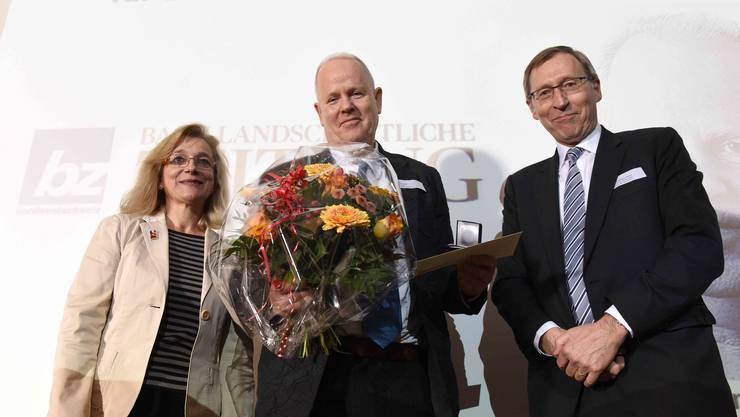 Kathrin Amacker, Präsidentin der Regio Basiliensis und ehemaliger Regierungsrat Basel-Stadt Hans Martin Tschudi überreichen Peter Schenk (Mitte) die Auszeichnung.