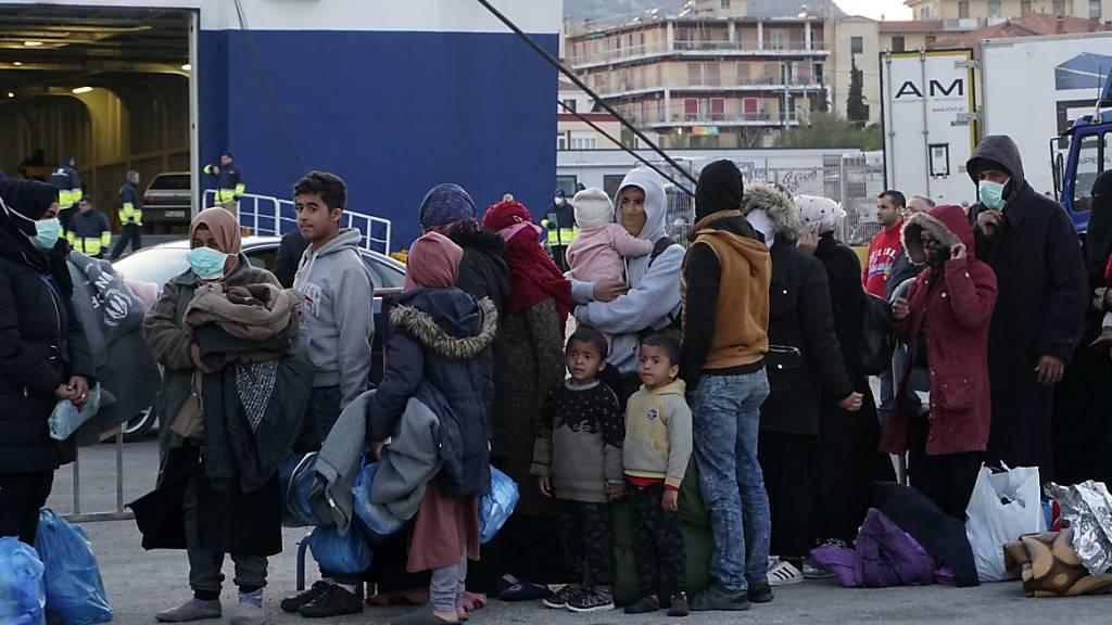 ARCHIV - Migranten stehen in einer Schlange, um im Hafen von Mytilene, auf der nordöstlichen Ägäisinsel Lesbos an Bord einer Fähre zu gehen. Foto: Vangelis Papantonis/AP/dpa