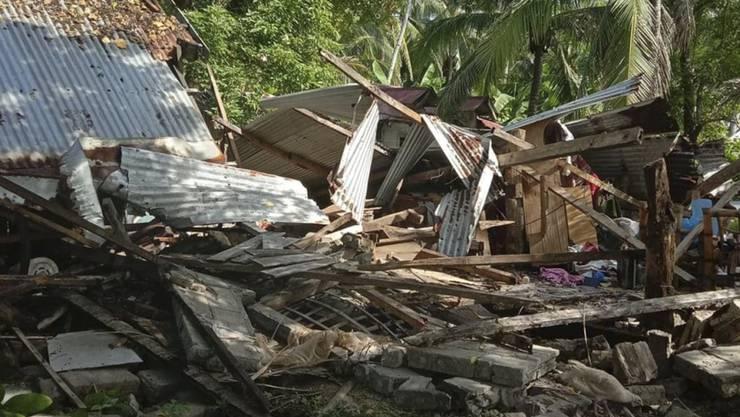 HANDOUT - Auf diesem vom philippinischen Roten Kreuz zur Verfügung gestellten Foto ist ein umgestürztes Haus zu sehen, nachdem sich ein schweres Erdbeben auf der philippinischen Insel Masbate ereignet hat. Foto: John Mark Lalaguna/Philippine National Red Cross/AP/dpa - ACHTUNG: Nur zur redaktionellen Verwendung im Zusammenhang mit der aktuellen Berichterstattung und nur mit vollständiger Nennung des vorstehenden Credits