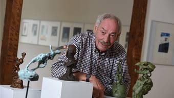 Der Maler und Zeichner Christoph Gloor inmitten seiner Ausstellung und neben seinem berühmten Schweizer mit Sackmessernase im Birsfelder Museum. Juri Junkov