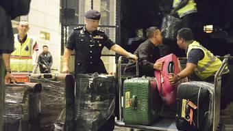 Polizisten verladen dutzende Kisten und Koffer voller Luxusartikel, die bei einer Razzia bei Malaysias Ex-Regierungschef Najib gefunden wurden.