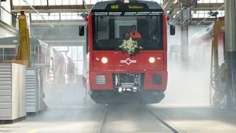 Die neue Uetlibergbahn fährt ein mit viel Rauch.