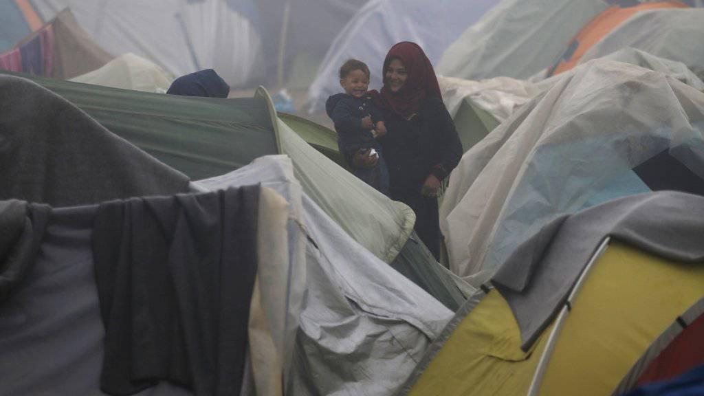 Eine Frau trägt vor einem Zelt im Flüchtlingslager von Idomeni im Norden Griechenlands ein Kleinkind auf den Armen.