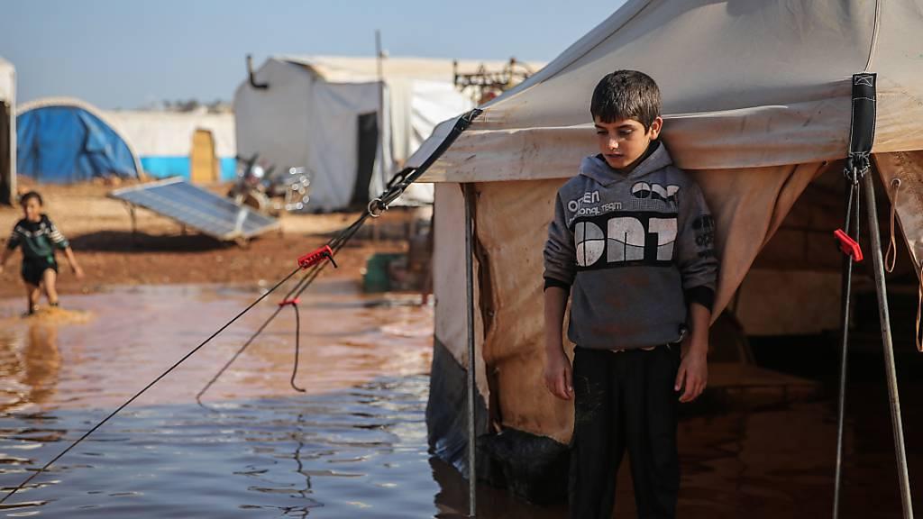 ARCHIV - Ein syrischer Junge steht in einem Flüchtlingslager, das vom Regen überflutet wurde, inmitten des schlammigen Wassers vor seinem Zelt. Foto: Anas Alkharboutli/dpa