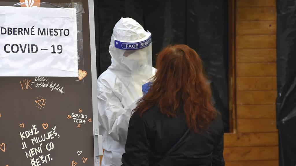 Ein Mediziner in Schutzkleidung macht an einer Corona-Teststation einen Abstrich bei einer Frau. In der Slowakei werden die Corona-Massentests fortgesetzt. Foto: Miroslava Mlyn·rov·/TASR/dpa