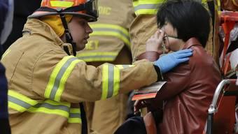 Feuerwehrmann hilft einer Frau bei der Evakuierung der Metro