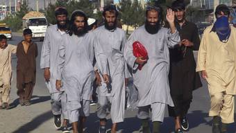 Afghanische Taliban-Gefangene, die aus dem Bagram-Gefängnis entlassen wurden, gehen eine Straße entlang. Foto: Rahmat Gul/AP/dpa