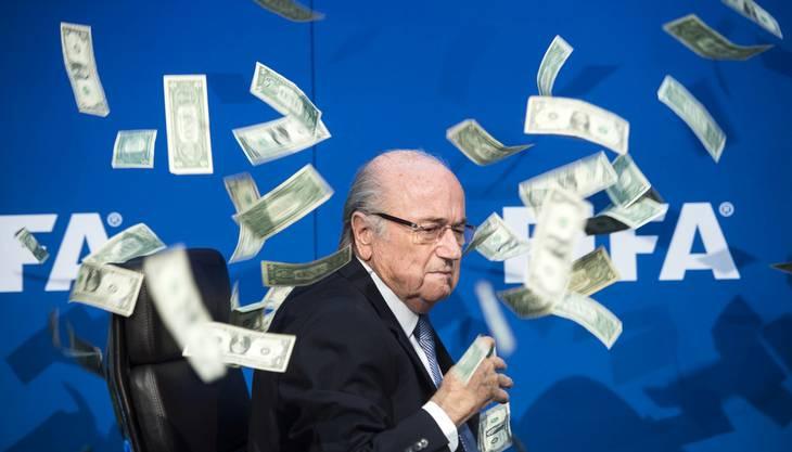 Sepp Blatter wird am 20. Juli an einer Pressekonferenz von Komiker Simon Brodkin mit Geld beworfen.