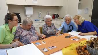 Die Tagesgäste schauen am grossen Tisch die Fotos aus früheren Jahren an. Alle Aufnahmen werden dann auf ein oranges Plakat geklebt.