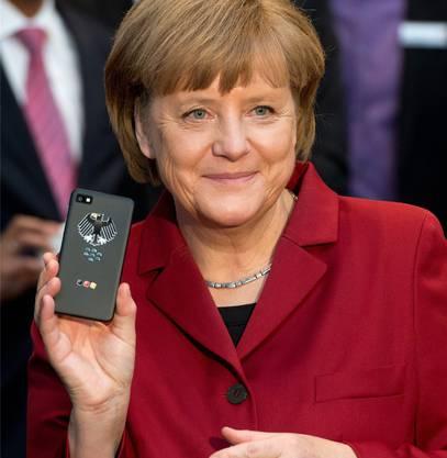 Merkel präsentiert stolz ihr ahörsicheres Handy.