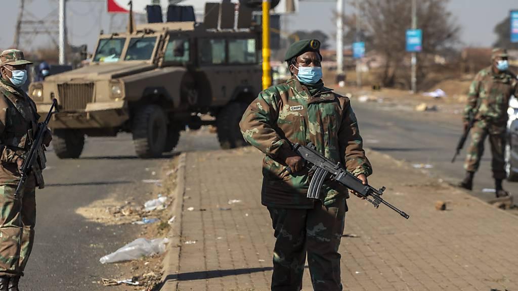 Bewaffnete Soldaten patrouillieren außerhalb eines Einkaufszentrums. In Südafrika setzten sich die tagelangen gewalttätigen Proteste fort. Foto: Themba Hadebe/AP/dpa