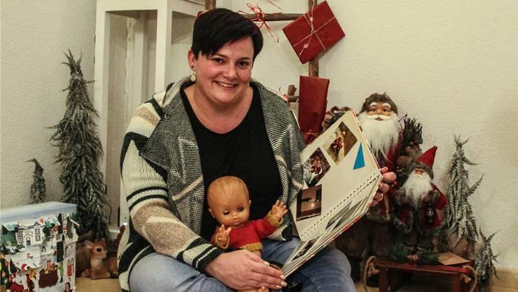 Corinne Koch betrachtet Fotos von früheren Weihnachten, auf ihrem Schoss sitzt «Tägerli», ihr schönstes Geschenk.