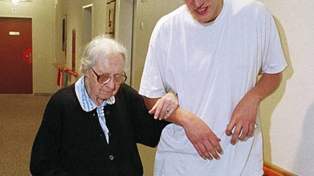 Zivi hilft älterer Frau beim Gehen