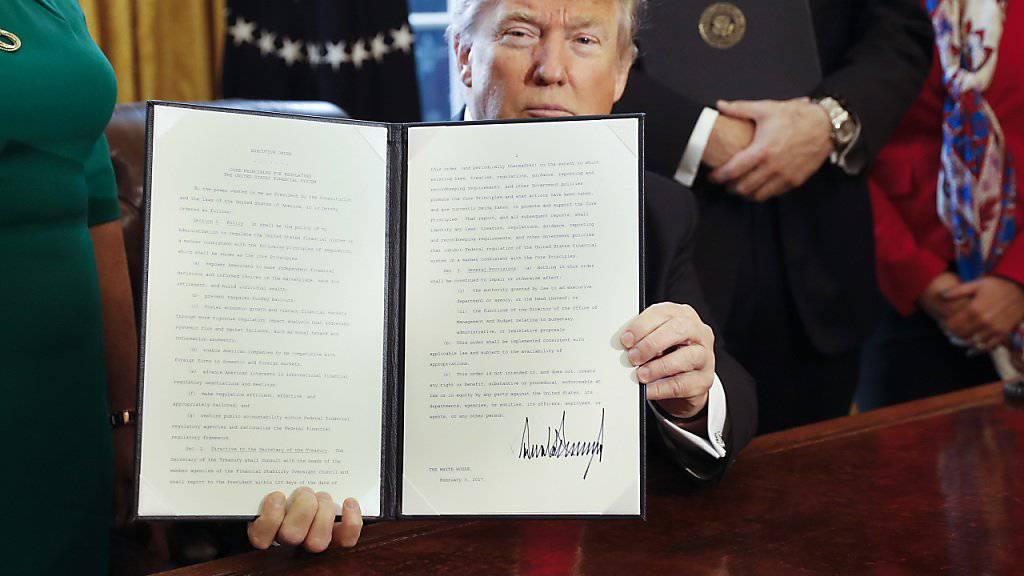 US-Präsident Trump präsentiert den Erlass zur Überprüfung der Bankenregulierung, nachdem er ihn unterschrieben hat.