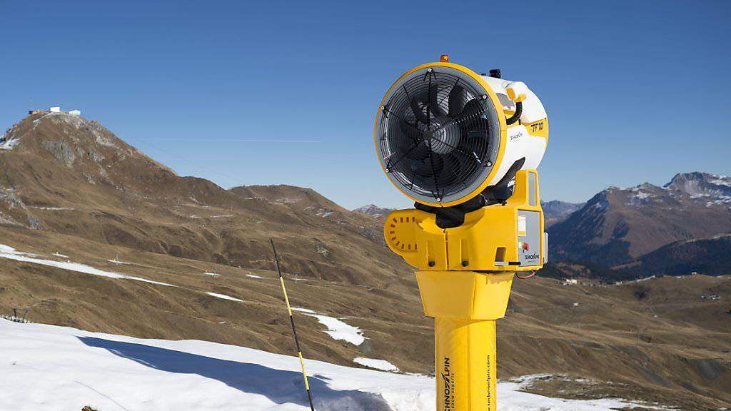 Eine Schneekanone neben einer geöffneten Piste in Arosa. Etwa ein Dutzend Bündner Bergbahnen und Tourismusbetriebe haben wegen des fehlenden Schnees Kurzarbeit angemeldet. (Symbolbild)