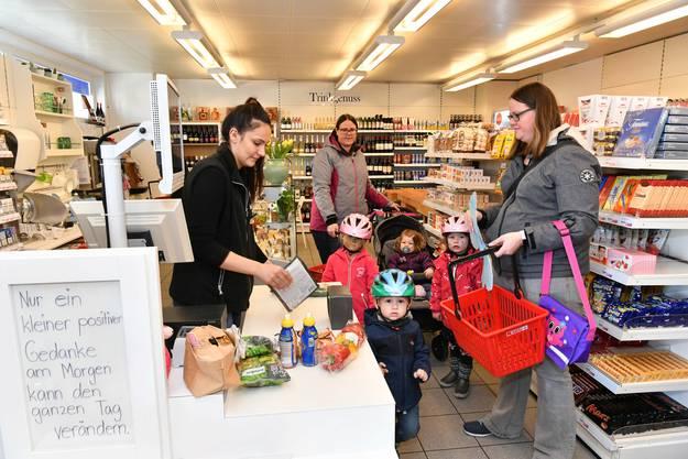 Eine Mutter kauft mit ihren Kindern ein.
