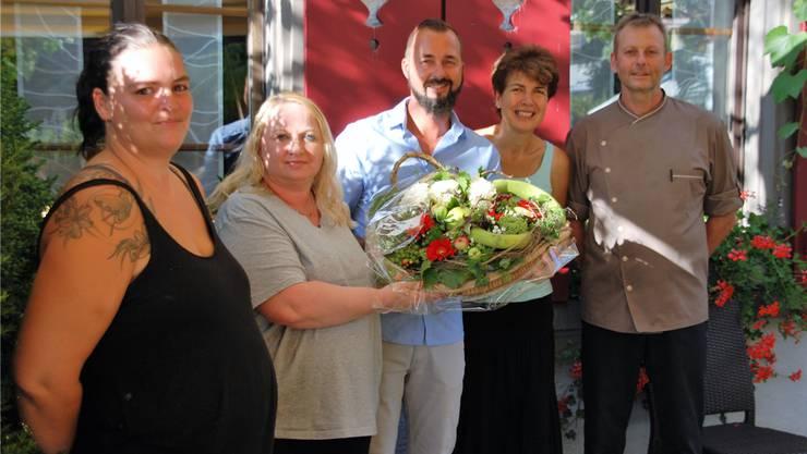 Béatrice und Pierre Arn (r.) erhalten Blumen von Ammann Roger Berglas (Mitte) und den Gemeinderätinnen Angela Ringger und Corinne Schneider (l.).