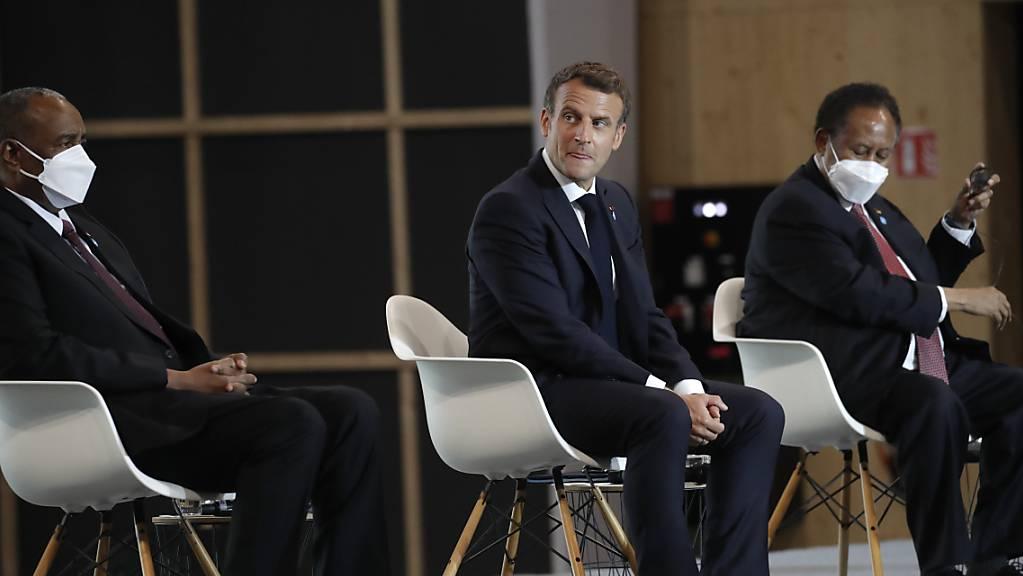 Emmanuel Macron (M), Präsident von Frankreich, Abdalla Hamdok (r), Premierminister des Sudan, und General Abdel Fattah Abdelrahman Burhan, Vorsitzender des sudanesischen Souveränitätsrats, nehmen an einer internationalen Konferenz über den Sudan teil. Eine internationale Konferenz zur Unterstützung des Sudans soll den Entschuldungsprozess des Landes einleiten.