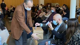 Der neue Kirchenpfleger Michele Aggiato, der später als Kirchenpflegepräsident gewählt wurde, wirft bei der Wahl der neuen Kirchenpflegerin Judith Tanner seine Stimme in die Stimmzettel-Box, die von Stimmenzähler Eugen Eberhard gehalten wird.