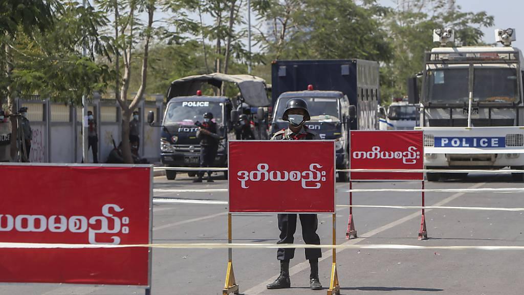 Polizisten stehen Wache auf einer abgesperrten Straße in Mandalay. Foto: Str/AP/dpa
