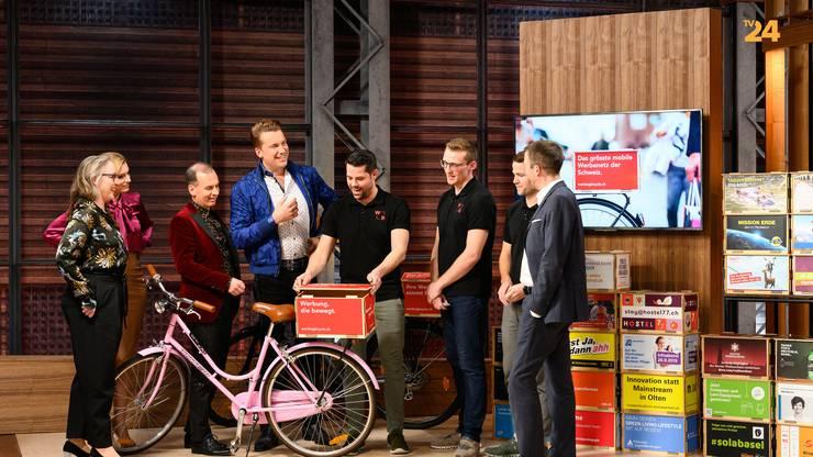Die drei Gründer von «Working Bicycle» erklären ihren potentiellen Investoren die mobile Werbebox.