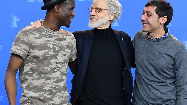 """Der Schweizer Regisseur Markus Imhoof zwischen den beiden Hauptdarstellern von """"Eldorado"""" Akhet Tewende (l) und Raffaele Falcone (r). (Archiv)"""