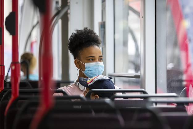 Eine Frau trägt in einem Bus in Bern eine Maske.
