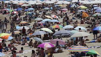 Grossandrang an spanischen Stränden: Touristen liegen in Barcelona an der Sonne.