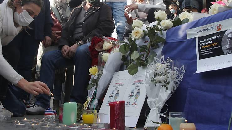 Eine Frau zündet eine Kerze für den ermordeten Lehrer Samuel Paty an. Foto: Michel Euler/AP/dpa