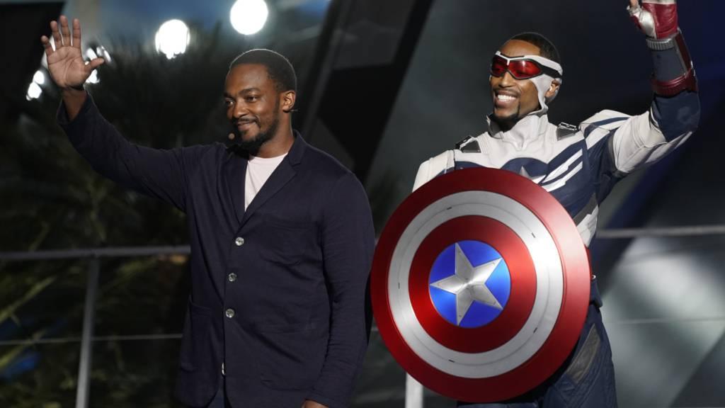 ARCHIV - US-Schauspieler Anthony Mackie (l) und sein Charakter Captain America winken während der Einweihungsfeier des «Avengers Campus» in Disneys California Adventure Park. Foto: Chris Pizzello/Invision/AP/dpa