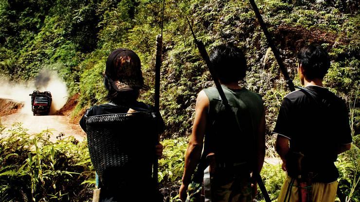 Bedrohtes Zuhause Indigene vom Stamm der Penan beobachten einen Lastwagen, der Regenwaldholz aus Sarawak abtransportiert.