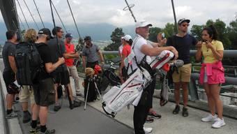 Golfspieler und Fernsehteam bereiten sich auf den Abschlag von der Brücke vor.