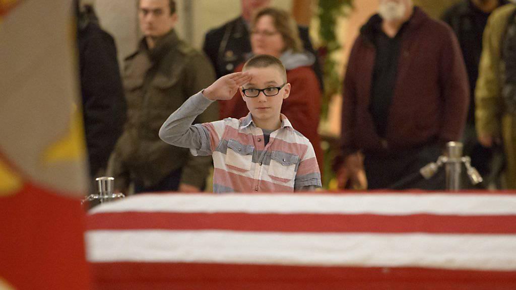 Abschied von einer Legende: Ein junger Trauergast salutiert beim Sarg des verstorbenen US-Raumfahrtpioniers John Glenn in Colombus.