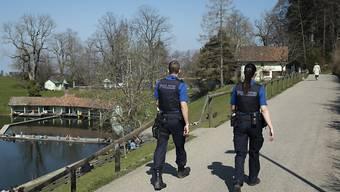 """Eine Patrouille der Stadtpolizei St. Gallen im Naherholungsgebiet """"Drei Weieren""""."""