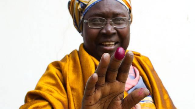 Eine Senegalesin zeigt ihre rot gefärbte Fingerspitze, nachdem sie ihre Stimme abgegeben hat