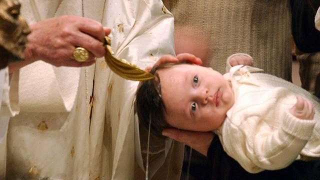 Ein Kind wird in der Kirche getauft (Symbolbild)
