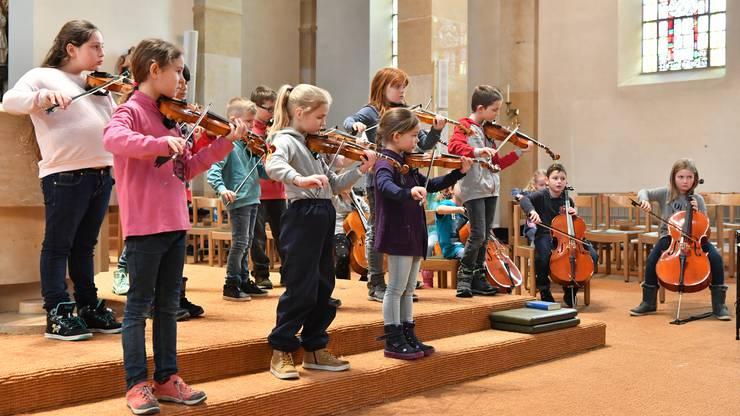 17 Kinder spielen Geige, Bratsche und Cello und singen dazu.