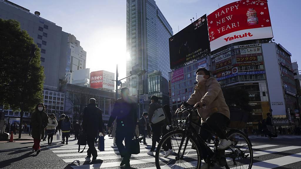 Menschen mit Mund-Nasen-Schutz überqueren die Straße im Stadtteil Shibuya. Wenige Monate vor den geplanten Olympischen Spielen in Tokio ist Zahl der Corona-Neuinfektionen in der japanischen Hauptstadt auf einen neuen Rekord gestiegen. Foto: Eugene Hoshiko/AP/dpa