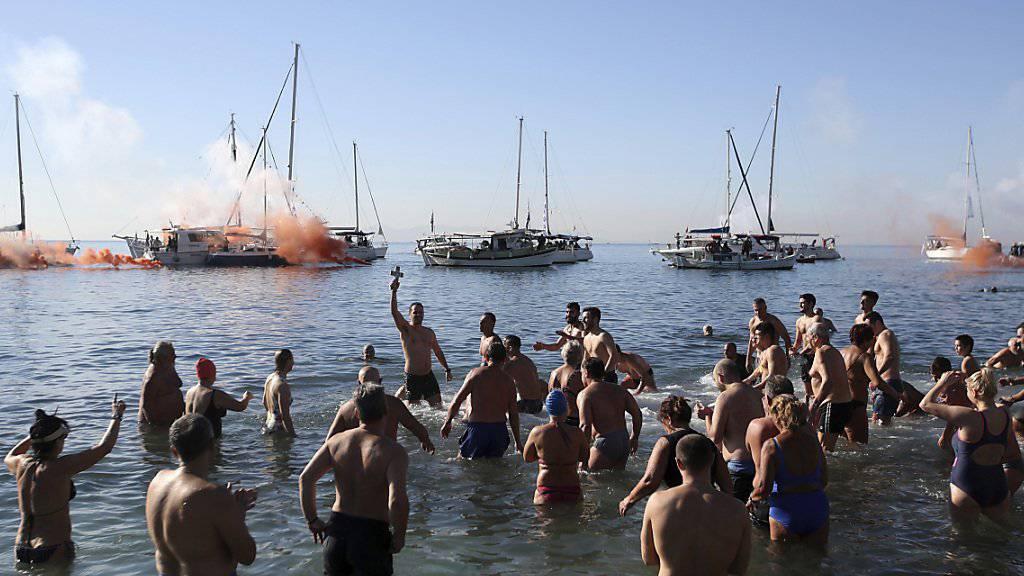 Eine Gruppe griechisch-orthodoxer Christen feiert die Taufe Jesu - der Glücklich, der das Kreuz im Wasser gefunden hat, soll im neuen Jahr bessere Chancen auf Glück und Gesundheit haben.