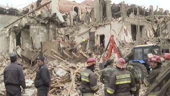 Rettungssanitäter und Zivilisten stehen vor den Trümmern eines zerstörten Gebäudes, nachdem die Stadt während der Kämpfe um das separatistische Gebiet Berg-Karabach von armenischer Artillerie beschossen wurde (Ausschnitt aus einem Video). Mehrere Zivilisten wurden getötet und Dutzende verwundet. Foto: Uncredited/AP/dpa