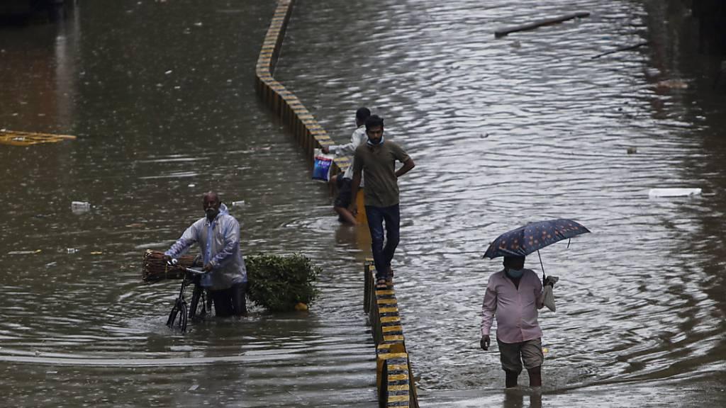 Menschen bahnen sich in Mumbai ihren Weg durch eine überschwemmte Straße nach starken Regenfällen. Foto: Rajanish Kakade/AP/dpa