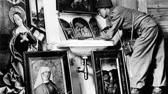 Geraubt oder nicht? Ein US-Soldat betrachtet im Mai 1945 Bilder, die Reichsmarschall Hermann Göring während des Krieges zusammentrug.