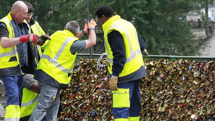Angestellte der Stadt Paris entfernen an der Fussgängerbrücke Pont des Arts die Gitter sowie die daran angebrachten Liebesschlösser.