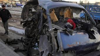 Ein Mann in der Nähe von Bagdad inspiziert ein explodiertes Auto