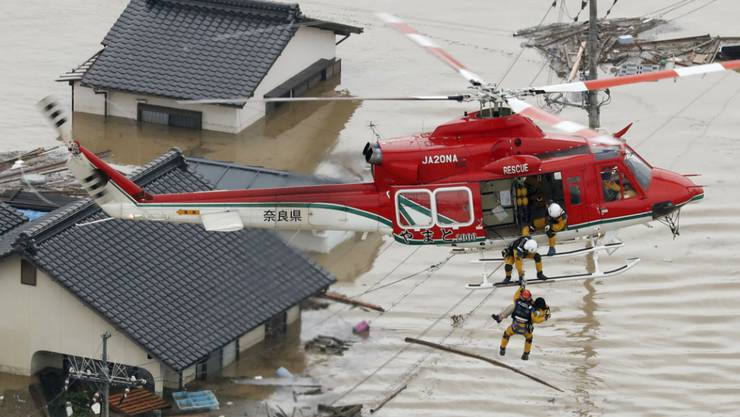 Schwere Überschwemmungen im Süden Japans: Rettungsteams bringen Einwohner per Helikopter in Sicherheit.